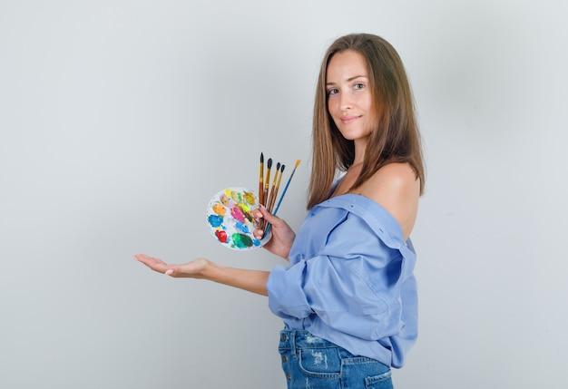 Giovane femmina che tiene i pennelli e la tavolozza in camicia, pantaloncini e sembra felice