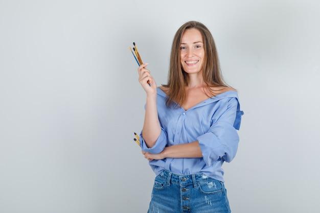 Молодая женщина держит кисти для рисования в рубашке, шортах и выглядит веселой