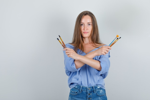 Молодая женщина держит кисти для рисования в рубашке, шортах и выглядит уверенно