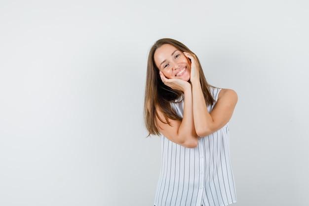 Tシャツの頬に手のひらを持って幸せそうに見える若い女性。正面図。