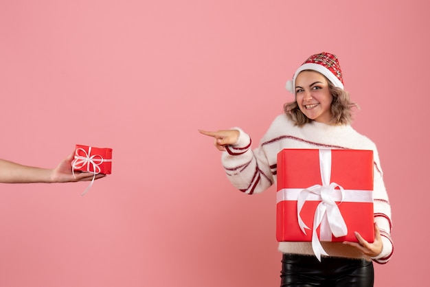 ピンクの男性からプレゼントを保持し、プレゼントを受け入れる若い女性