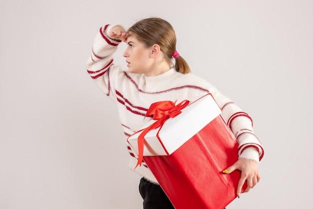 화이트에 거리를보고 선물 상자를 들고 젊은 여성