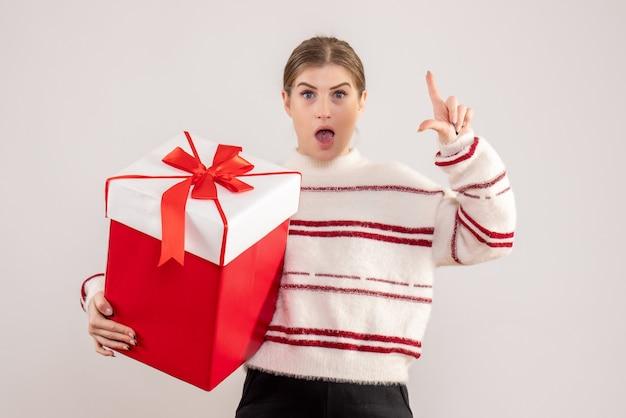 Молодая женщина держит подарок в коробке на белом