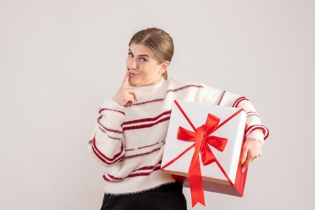 白のボックスに存在を保持している若い女性