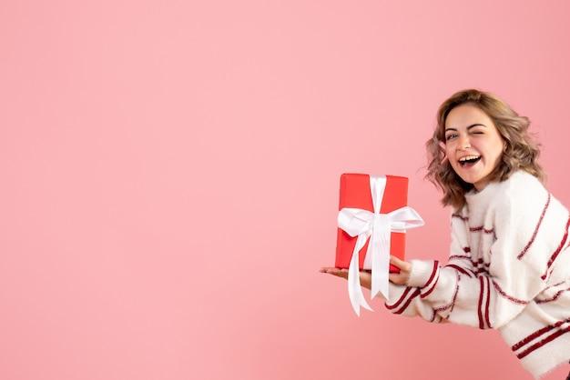 Молодая женщина держит подарок на розовом
