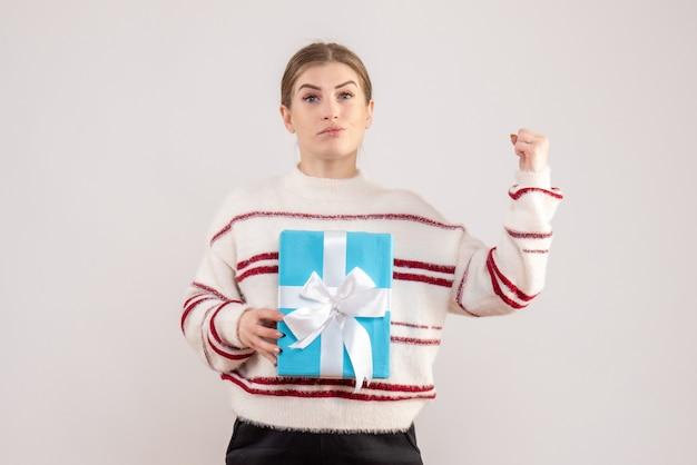 白でプレゼントを保持している若い女性
