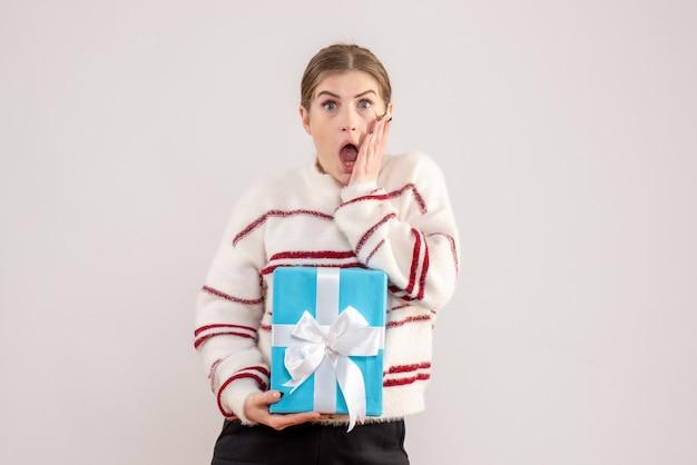 Молодая женщина держит подарок на белом