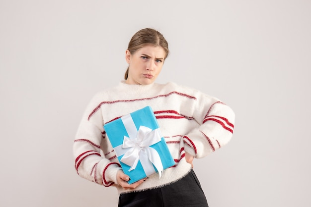 Young female holding present on white