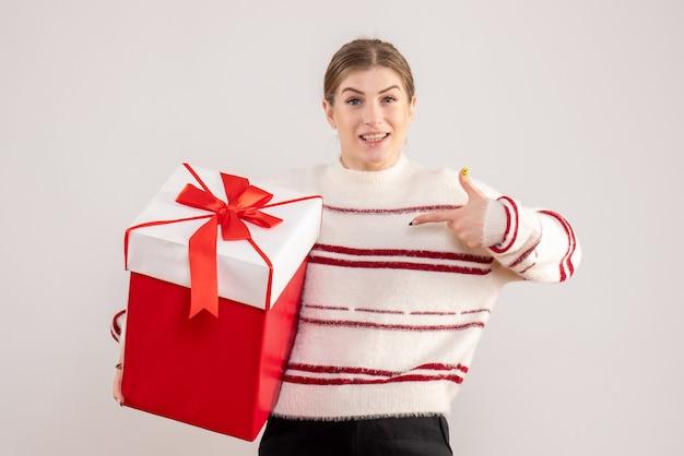 白に赤いプレゼントを保持している若い女性
