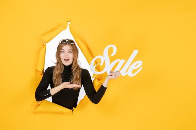 Giovane donna azienda vendita iscritto attraverso carta strappata buco nel muro