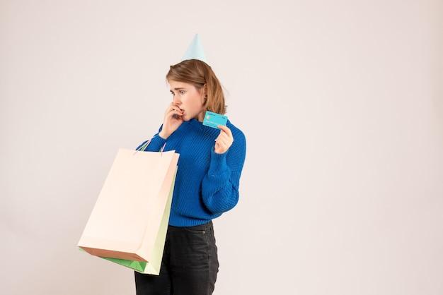 Молодая женщина держит пакеты с покупками и банковскую карту на белом