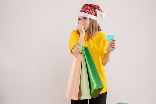 Young female holding shopping packages and bank card scared on white