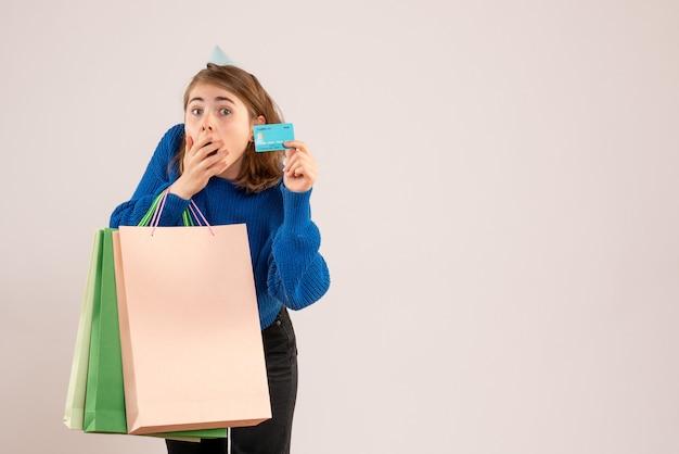 Giovane femmina che tiene i pacchetti della spesa e carta di credito su bianco
