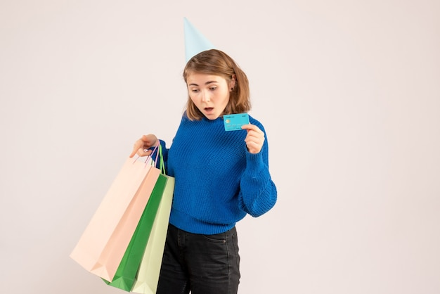 Young female holding shopping packages and bank card on white