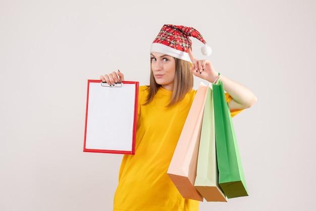 Giovane femmina che tiene i pacchetti della spesa e nota su bianco
