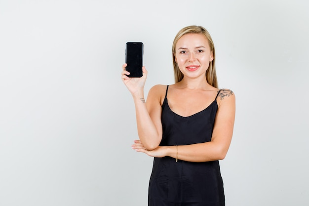 黒の一重項でスマートフォンを保持し、陽気に見える若い女性