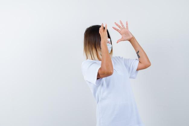T- 셔츠, 마스크에 뭔가 들고 자신감을 찾고 젊은 여성. 전면보기.