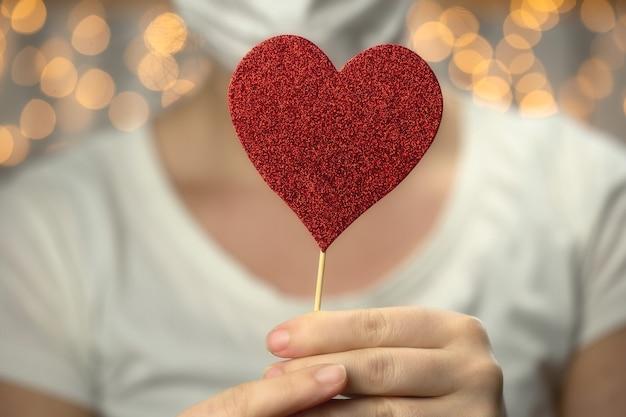 Молодая женщина держит сверкающее красное сердце в белой защитной медицинской маске от коронавируса