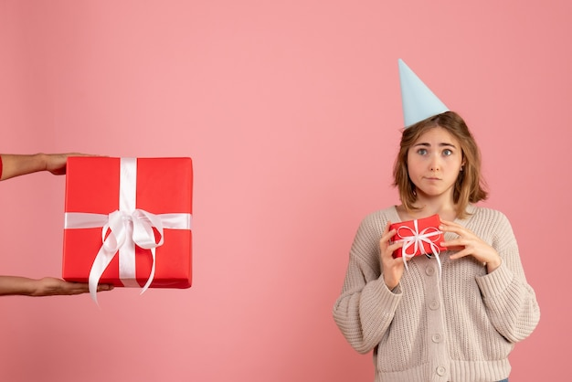 Young female holding xmas present and accepting gift from male on pink