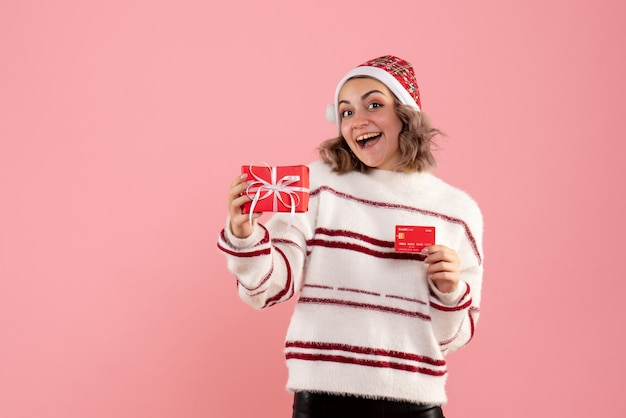 Young female holding xmas present and bank card on pink