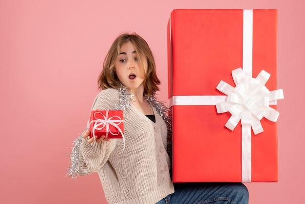 ピンクのクリスマスプレゼントボックスを保持している若い女性