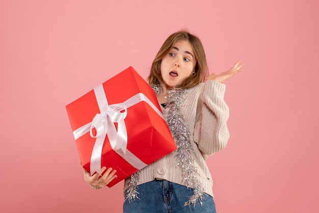 Young female holding xmas present in her hands on pink