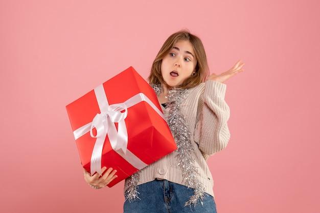 Молодая женщина держит в руках рождественский подарок на розовом