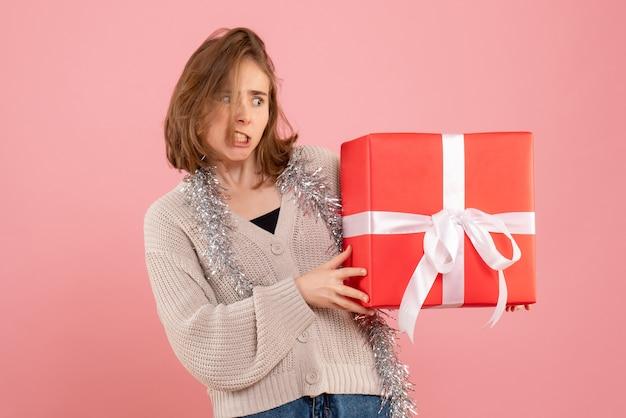 핑크에 그녀의 손에있는 크리스마스를 들고 젊은 여성