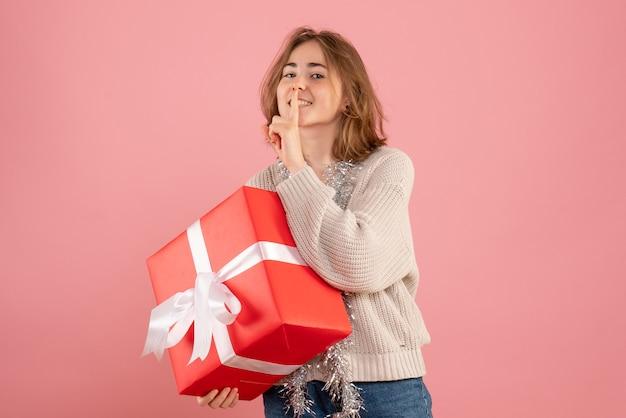 Молодая женщина держит рождественский подарок на розовом