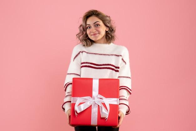 ピンクにクリスマスプレゼントを保持している若い女性