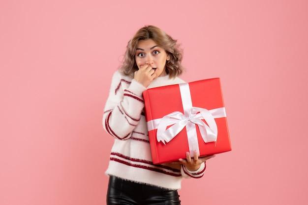 핑크에 크리스마스 선물을 들고 젊은 여성