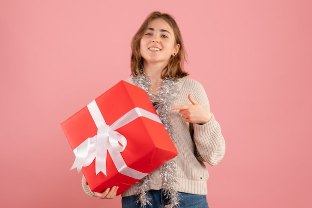 Young female holding xmas present on pink