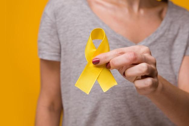 Молодая женщина держит символ осведомленности о желтой золотой ленте для эндометриоза, предотвращения самоубийств, рака костей саркомы, рака мочевого пузыря, рака печени и концепции детского рака. здравоохранение. закройте вверх.