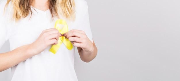 Молодая женщина держит символ осведомленности о желтой золотой ленте для эндометриоза, предотвращения самоубийств, рака костей саркомы, рака мочевого пузыря, рака печени и концепции детского рака.