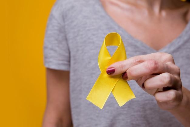 Молодая женщина держит символ осведомленности о желтой золотой ленте для эндометриоза