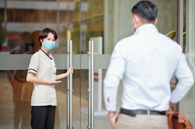 医療マスクの若い女性ホテルのコンシェルジュがゲストのためにドアを開け、彼を中に招待します