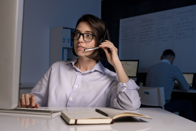 Young female hotline operator with headset speaking to clients online in front of computer screen