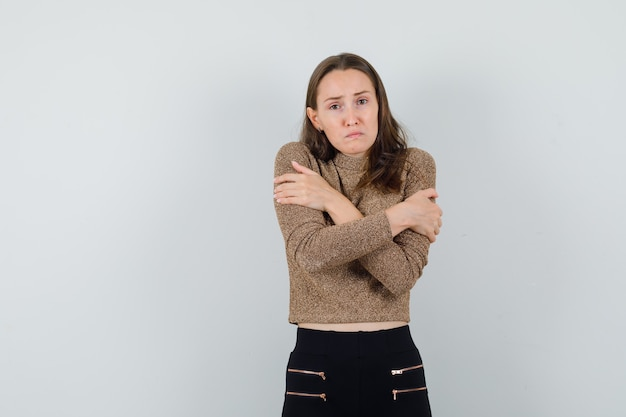 Young female hugging herself in blouse,skirt and looking worried , front view.