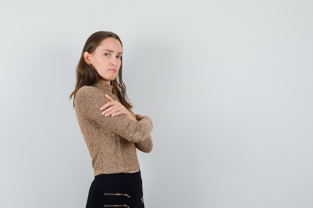 Young female hugging herself in blouse,skirt and looking worried. . space for text