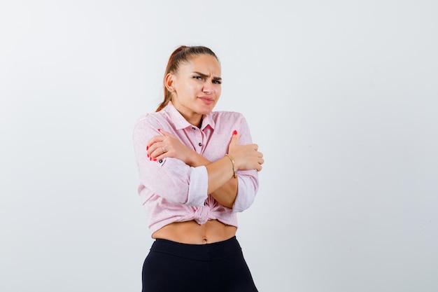 Молодая женщина обнимает себя в повседневной рубашке, штанах и выглядит охлажденной