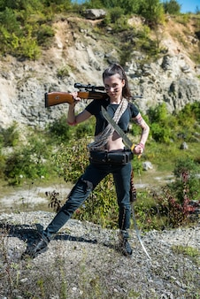 Young  female hunter in top with a rifle, in summer at nature. shooter