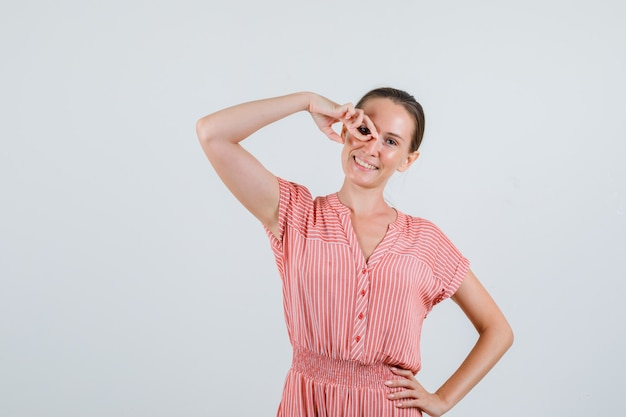 縞模様のドレスを着て、陽気に見える指でメガネを模倣する若い女性。正面図。