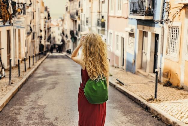 Молодая женщина в красном платье идет по дороге в окружении зданий под солнечным светом