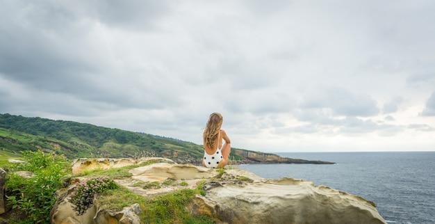 Молодая женщина в купальнике с точками сидит на скале у моря