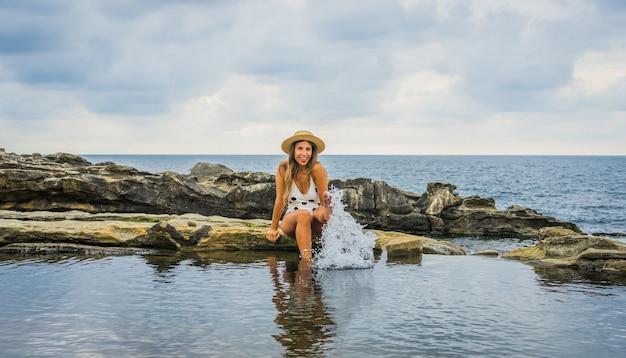 바다 근처 바위에 앉아 점이 있는 수영복을 입은 젊은 여성