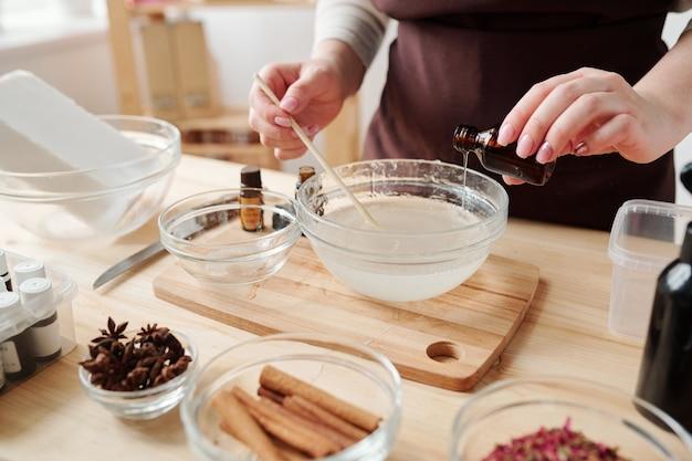 Молодая женщина в фартуке наливает одно из эфирных масел в жидкую мыльную массу в стеклянной посуде во время работы в студии