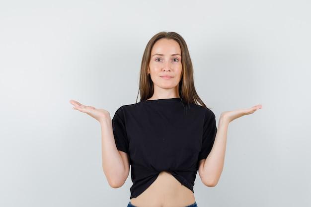 Молодая женщина в черной блузке делает жест весы и выглядит справедливо