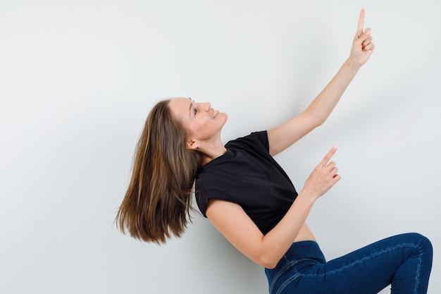 Молодая женщина в черной блузке, штаны направлены вверх, поднимая ногу и выглядят энергично