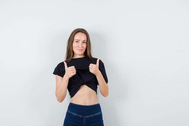 Молодая женщина в черной блузке, брюки показывает палец вверх и выглядит счастливой