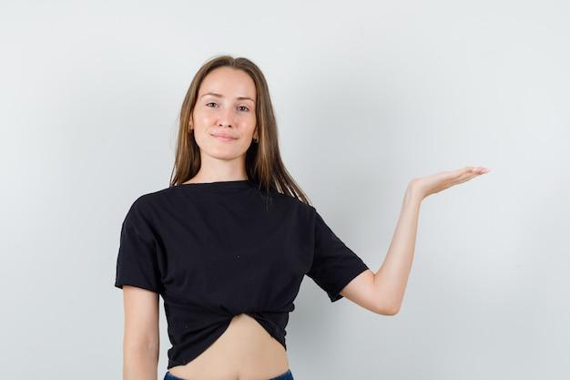 何かを持って自信を持って見えるように手のひらを上げる黒いブラウスの若い女性